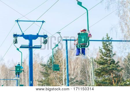 Skier climbs on the chair lift to the track.