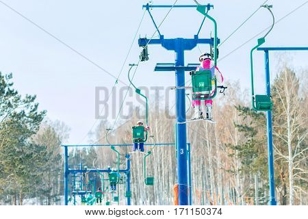Skier Climbs On The Chair Lift To The Track