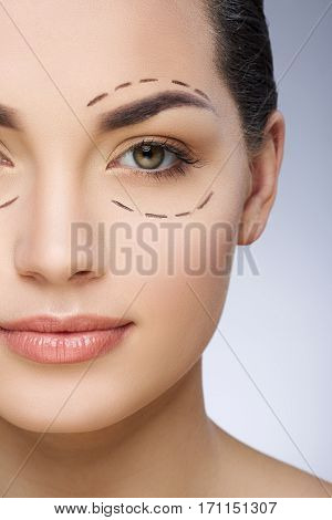 Dashed lines around eyes of girl. Beautiful girl smiling. Plastic surgery, beauty portrait, half face, closeup