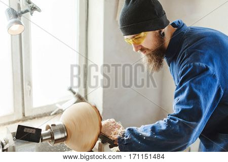 Man with a beard wearing blue jeans suit, black hat and protecting yellow glasses working with woodcarving machine, window at background, copy space.
