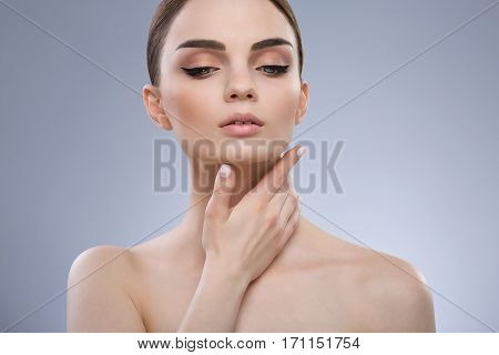 Make up model girl with brown hair fixed behind, dark eyebrows and naked shoulders looking down at gray studio background, portrait, copy space.