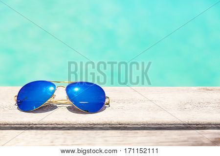 Blue sunglasses lying on a wooden deck
