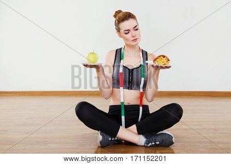 Fit girl wearing black snickers, leggings and dark short top sitting at gym in yoga position and holding two plates with fries and apple, looking at fries, copy space.