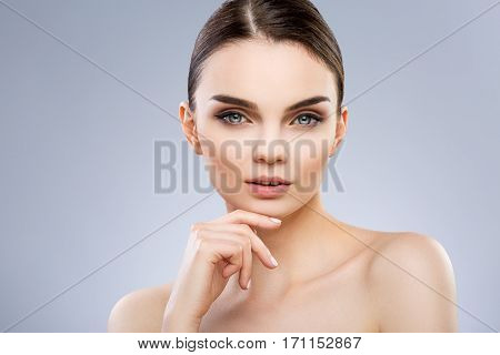 Beautiful model with big blue eyes and perfect make-up looking at camera. Fingers touching chin. Beauty portrait, head and shoulders, studio, indoor