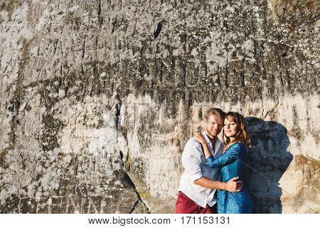 Nice couple standing near stone wall, outdoor. Man embracing his girlfriend's waist and looking down. Woman looking aside. Woman wearing blue dress and man wearing white shirt and claret trousers. Full body. Copyspace