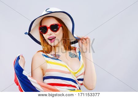 Cheerful girl with hat, striped dress and heart-shaped red sunglasses smiling widely and looking aside. Summer look. Studio, indoor, head and shoulders