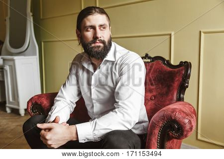 Handsome man sitting on red chair. Bridegroom looking aside. Fingers crossed. Man in white shirt with beard and moustache. Indoor, studio