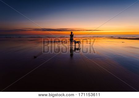 Silhouette of a woman taking a photo with her dog standing beside her on the beach during a vivid sunset. Western Australia, Australia.