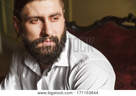 Portrait of handsome man sitting on red chair. Bridegroom looking aside. Man in white shirt with beard and moustache. Indoor, studio, closeup, portrait