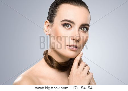 Model looking at camera and holding pigtail around her neck. Head a little bit aside. Looking lively, nice make-up. Beauty portrait, head and shoulders. Indoor, studio