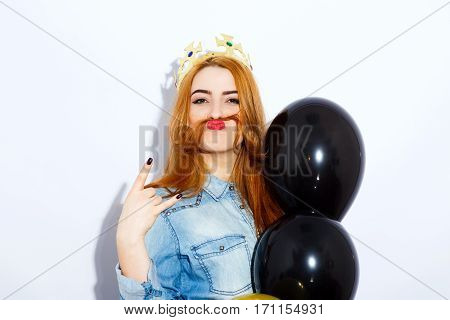 Funny teenage red-haired girl with long hair wearing blue jacket and crown holding balloons, red lips, black manicure, copy space, pathos emotion.