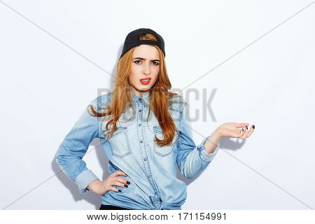Pretty teenage red-haired girl with long hair wearing blue shirt and black hat, red lips, black manicure, portrait, copy space, annoyed posing.