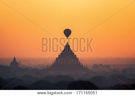 temples in Bagan with hot air balloon for traval on sun rise and mist Myanmar