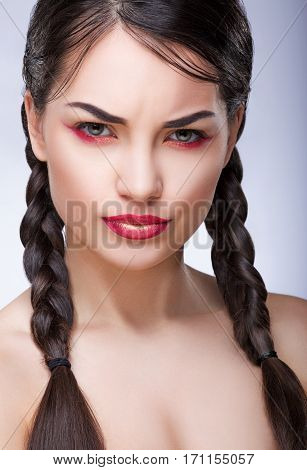 Beautiful girl with bright make-up frowning eyebrows. Lower eyelids colored in red. Braided hair. Beauty portrait, head and shoulders, studio