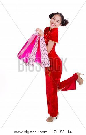 Beautiful Asia girl happy smile and shopping with Chinese traditional dress Cheongsam holding a shopping bag isolated on white background