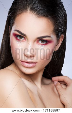 Girl with bright make-up looking at camera. Eyelids colored in red with little glittering stars. Loose hair. Hand near shoulder. Beauty portrait, head and shoulders, closeup, studio