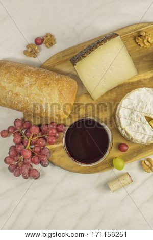 An overhead photo of a glass of red wine at a tasting, with bread, cheeses, grapes, and a wine cork, on a white marble table with copy space