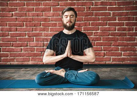 Handsome young bearded man with closed wearing black T-shirt sitting on blue matt doing yoga position at wall background, namaste mudra, copy space.