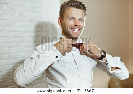 Pre-wedding preparation. Bridegroom fixing his vinous bow-knot and smiling. Wearing white shirt