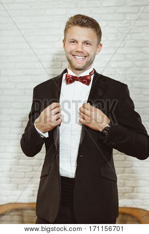 Pre-wedding preparation. Bridegroom wearing white shirt, vinous bow-knot, black jacket and smiling