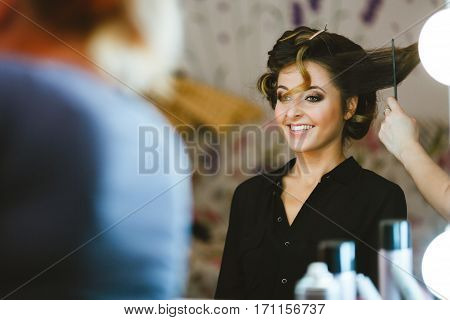 Pre-wedding preparation. Bride having her hair done. Fiancee smiling and looking at mirror. Waist up