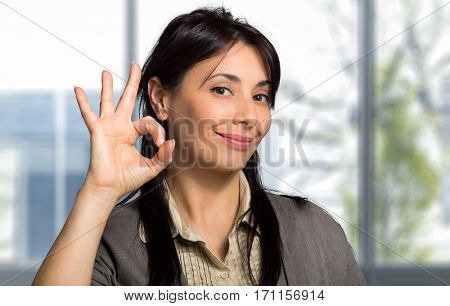 Portrait of beautiful girl showing OK sign and smiling