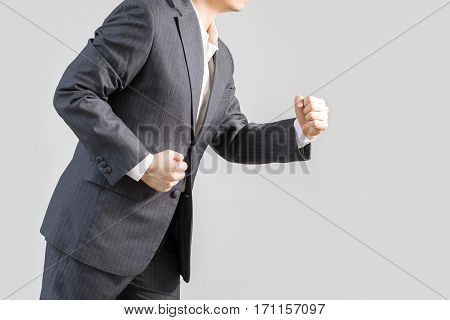 Studio shot of businessman in rush running forward isolated on white background illustrating success concept.