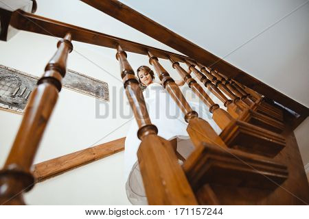 Pre-wedding preparation. Bride going down stairs. Fiancee on staircase. Bride wearing white wedding dress and veil. Indoor
