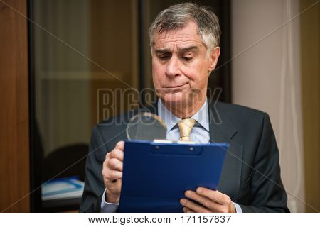 Businessman using a magnifying glass to read a document