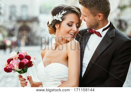 Wedding photo shooting. Bride and bridegroom in the city. Man embracing girl's waist from back. Holding bouquet. Bride with closed eyes. Outdoor, waist up, close up