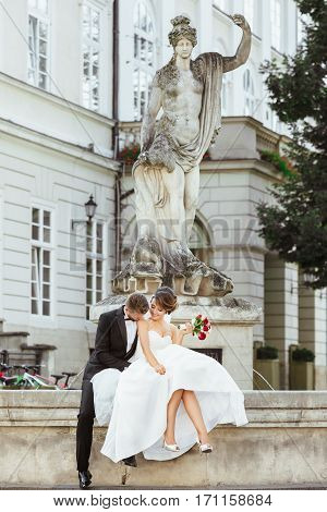 Wedding photo shooting. Bride and groom sitting near monument. Holding bouquet, bride smiling. Bridegroom kissing bride's shoulder. Outdoor, full body