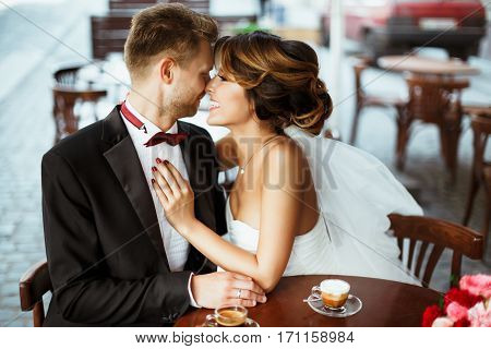 Wedding photo shooting. Bride and bridegroom sitting in cafe, embracing and smiling. Very close to each other.  Bouquet and coffee on table near them. Outdoor, waist up, profile