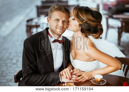 Wedding photo shooting. Bride and bridegroom sitting in cafe. Bride kissing bridegroom's forehead. Outdoor, waist up