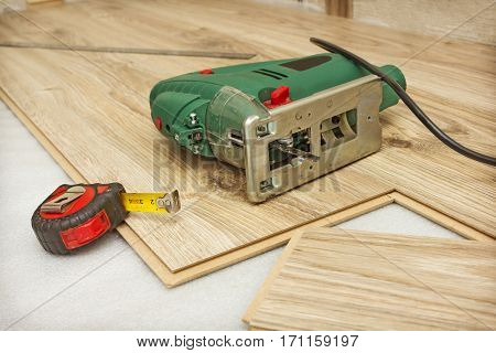 Jigsaw And Measuring Tape Lying On The Laminate