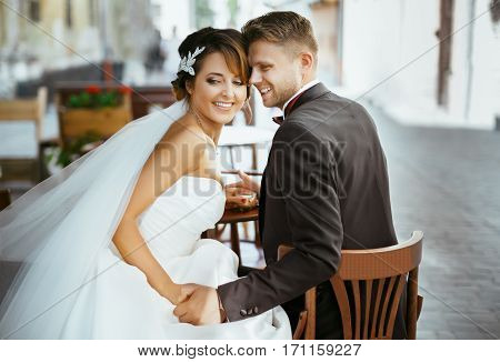 Wedding photo shooting. Bride and bridegroom sitting on chairs in cafe, looking aside and smiling. Outdoor, rear view