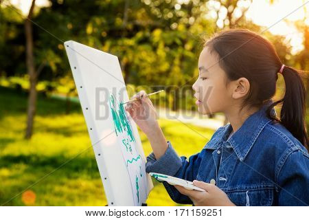little painter at work in the park with palette and canvas butter fly drawing with gild in park wint green outdoor backgroung kid teen and student concept.