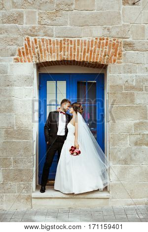 Bride and bridegroom standing near blue door, looking at each other and smiling. Bride embracing groom with one hand. Noses touching. Outdoor, full body, profile