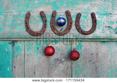 happy lucky Christmas and New year. Old rusty horseshoe and Christmas baubles on wooden door
