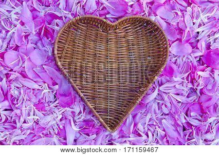 empty heart form wicker baske ton peony petal background