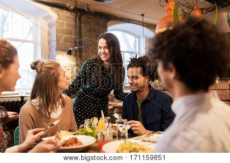 leisure, food, drinks, people and holidays concept - happy friends eating and drinking at restaurant