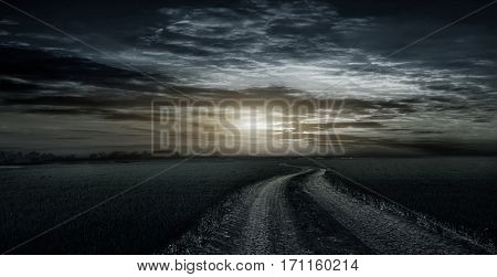 Beautiful, rural, dirt road between fields late at night on the background of beautiful sunset clouds.