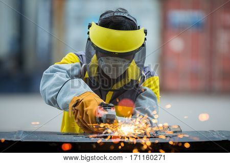 Employee grinding steel with sparks - focus on grinder. Production industrial operation factory repair safet job work working occupation and career concept poster