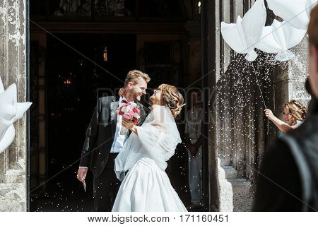 Wedding ceremony. Bride and groom embracing near church  and smiling. A lot of flowers, confetti and balloons. Guests around. Outdoor, profile