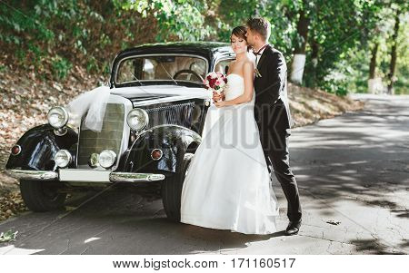 Wedding day. Bridegroom and bride standing near retro wedding car. Groom embracing and kissing bride. Outdoor, full body