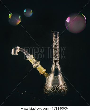 Detail of dabbing glass rig with soap bubbles floating - isolated over black background