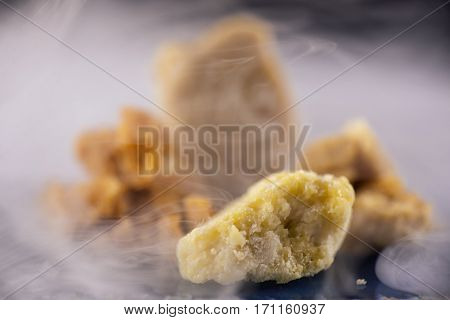 Four different kinds of marijuana extraction concentrate aka wax crumble on smoky background
