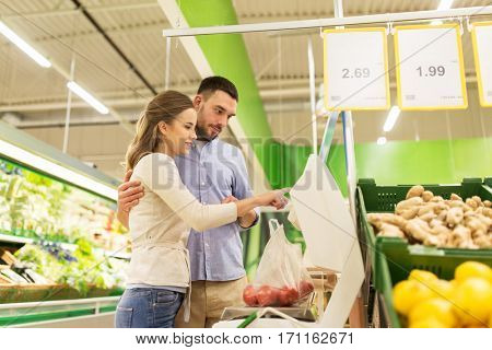 shopping, food, sale, consumerism and people concept - happy couple weighing tomatoes on scale at grocery store or supermarket