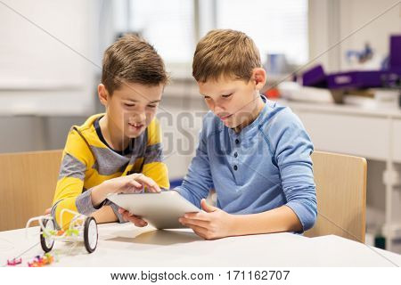 education, science, technology, children and people concept - happy boys or students with tablet pc computer programming electric toys at robotics school lesson