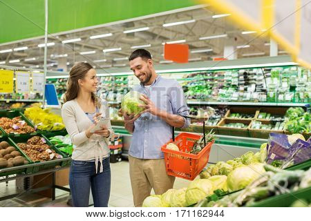 shopping, sale, consumerism and people concept - happy young couple with food basket and notebook at grocery store or supermarket
