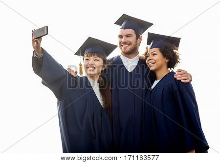 education, graduation, technology and people concept - group of happy international students in mortar boards and bachelor gowns taking selfie by smartphone outdoors